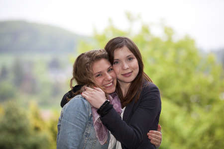 friend hug: Two hugging happy teenage girls posing cheek to cheek Stock Photo