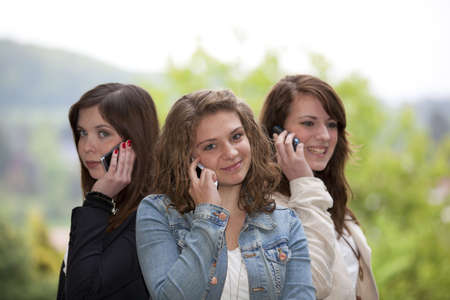 Three happy and smiling teenage girls with cellphones standing back to back photo