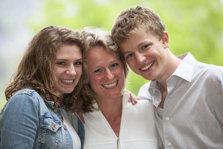 A happy smiling mother with her  teenage daughter and teenage son posing cheek to cheek