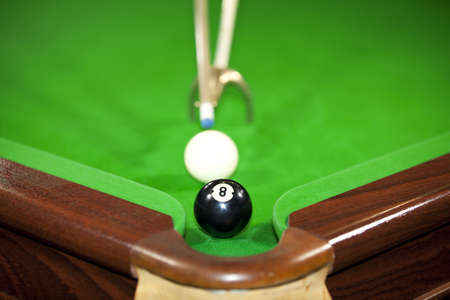 A billiard game situation with the billiard player being ready to hit the white ball to finish the game and pocket the black ball number eight photo
