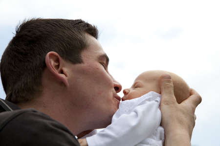A proud young father kissing his 7 weeks old crying daughter on her mouth photo