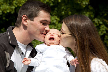 A young father and a young mother kissing their crying 7 weeks old daughter on her cheeks