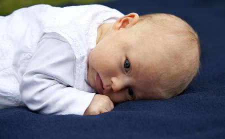 nursling: A cute 7 weeks old baby girl lying on a blue blanket