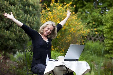 Eine jubelnden schöne Reife blond Frau sitzen in Ihrem Garten auf Ihrem laptop