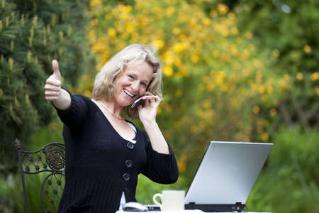 A smiling beautiful mature blond woman with a cellphone sitting in her garden at her laptop and posing with the thumbs up sign