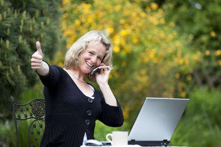 Eine lächelnd schöne Reife blond Frau mit einem Handy sitzen in Ihrem Garten auf Ihrem Laptop und posiert mit dem Daumen hoch Zeichen