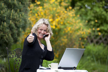 A smiling beautiful mature blond woman with a cellphone sitting in her garden at her laptop and posing with the thumbs up sign photo