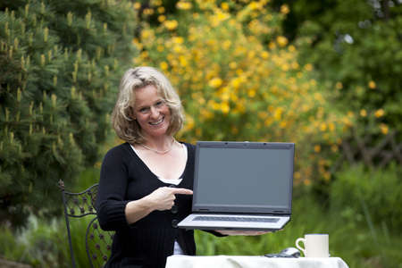 A smiling beautiful mature blond woman sitting in her garden presenting her laptop and pointing at it photo