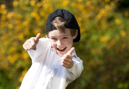 Ein lachend gut aussehend acht Jahre alte Junge mit einer Kappe, posiert mit beiden Daumen bis