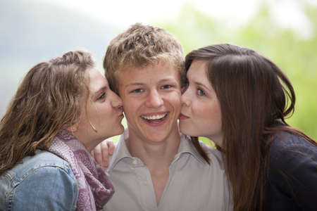 happy teenager being kissed by two teenage girls