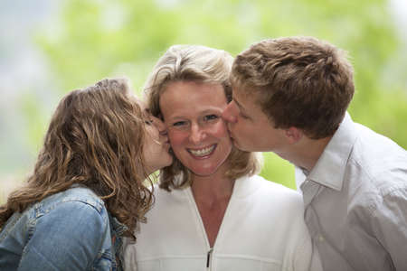 A happy smiling and laughing mother being kissed by her teenage daughter and teenage son