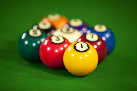 Nine billiard balls on a billiard table with the focus on the yellow ball number one photo