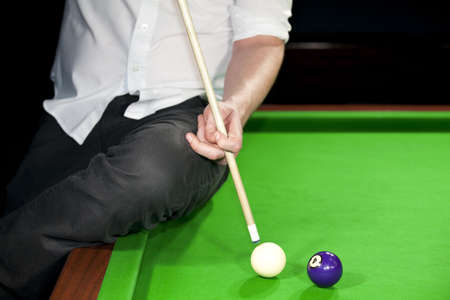 A professional billiard player showing how to play a curve ball photo