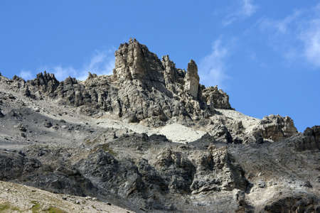 a rock formation in the Alps of South Tirol, photographed in the summer with blue sky and clouds in the background photo