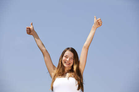 A smiling beautiful young woman posing with both thumbs up, photographed in the summer sun with blue sky in the background photo