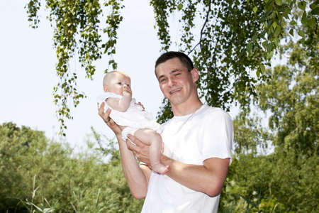 nursling: A happy smiling and proud young father holding his 15 weeks old baby girl