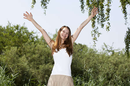 A smiling and cheering beautiful young woman raising her hands photo