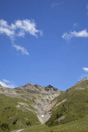vanished: A moraine of a vanished glacier in the Alps in South Tirol, photographed in the summer with blue sky and some tiny clouds in the background
