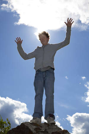 A back lighted shot of a smiling 14 years old teenager raising his arms, photographed in the summer with blue sky and clouds in the background photo