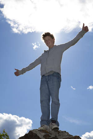 A back lighted shot of a smiling 14 years old teenager posing with both thumbs up, photographed in the summer with blue sky and clouds in the background photo