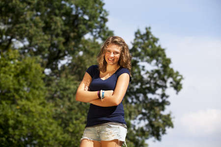 a beautiful blond laughing teenage girl posing with her arms crossed photo