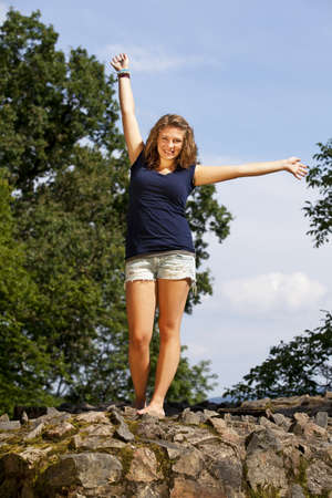 a beautiful blond cheering teenage girl posing in the summer sun while standing on a wall photo