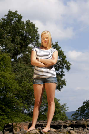 short shorts: a beautiful cool looking blond  teenage girl photographed in the summer sun with trees and blue sky with clouds in the background