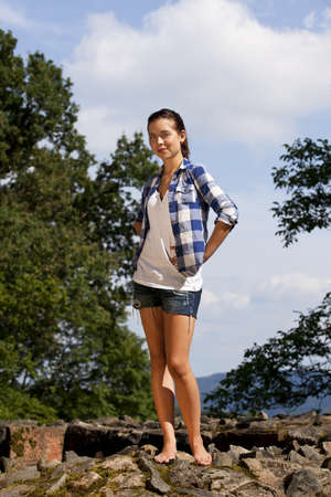 short shorts: A beautiful brunette smiling teenage girl posing in the summer sun, photographed with trees and blue sky with clouds in the background