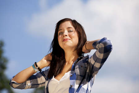 a beautiful brunette smiling teenage girl posing with her arms crossed behind her head Stock Photo - 7757830