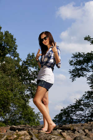 short shorts: a cool and smiling brunette teenage girl with sunglasses posing in the summer sun, photographed with trees and blue sky with clouds in the background Stock Photo
