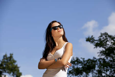 a cool brunette teenage girl with sunglasses posing in the summer sun, photographed with trees and blue sky with clouds in the background photo