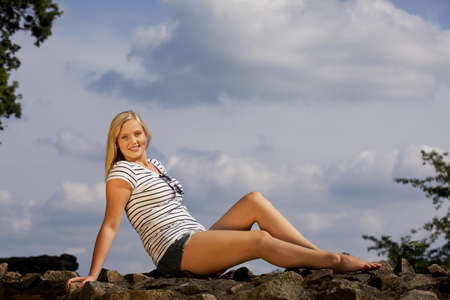 a beautiful blond smiling teenage girl sitting on a wall, photographed in the summer sun with cloudy sky in the background photo