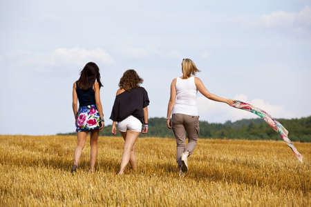 drei teenage Girls walking away, fotografiert in den späten Abendsonne auf ein Hektar Lizenzfreie Bilder