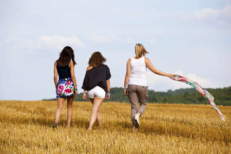 three teenage girls walking away, photographed in the late evening sun on an acre