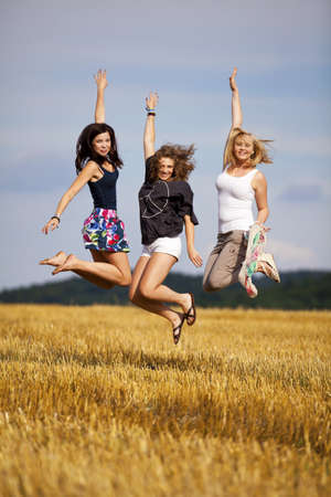 short shorts: three happy and jumping teenage girls, photographed in the late evening sun on an acre Stock Photo