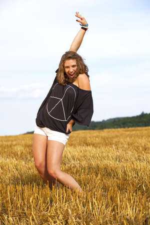 a beautiful blond cheering teenage girl photographed during late evening sun on an acre Stock Photo - 7758546