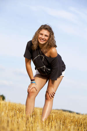a beautiful blond smiling teenage girl photographed in the late evening sun on an acre photo