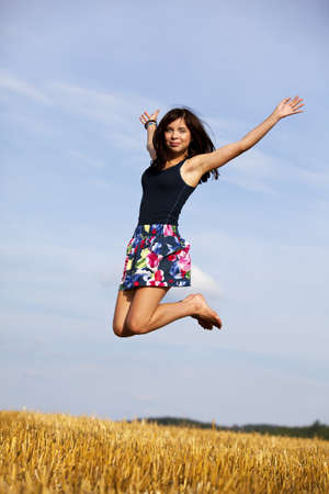 a happy and jumping brunette teenage girl photographed during late evening sun on an acre photo