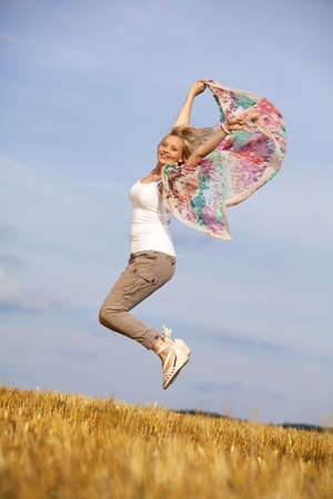 a happy and jumping blond teenage girl photographed during late evening sun on an acre photo