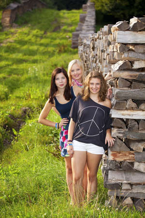 short shorts: three happy and smiling teenage girls photographed standing next to a stack of wood