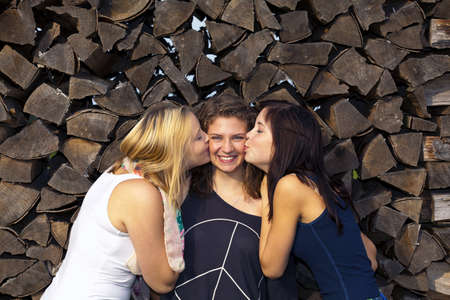 two teenage girls kissing their laughing girl friend in the middle on her cheeks photo