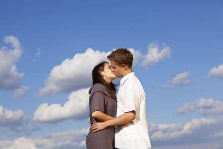 Ein kissing Teenager Paar mit blauer Himmel und Wolken im Hintergrund fotografiert  Lizenzfreie Bilder