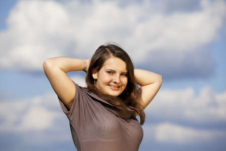 A beautiful and smiling teenage girl posing with her arms crossed behind her head, photographed with blue sky and clouds in the background photo