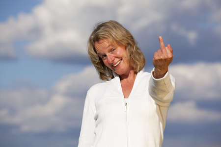 fingers on top: A beautiful smiling mature blond woman showing her middle finger, photographed with cloudy sky in the background Stock Photo