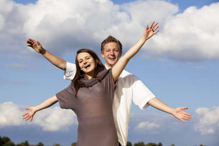 A cheering happy teenage couple, photographed with blue sky and clouds in the background photo