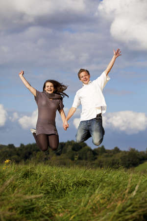 A happy and jumping teenage couple, photographed on a meadow with trees, blue sky and clouds in the background