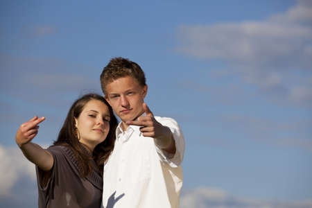 An arrogant teenage couple showing their middle fingers, photographed with blue sky and clouds in the background photo