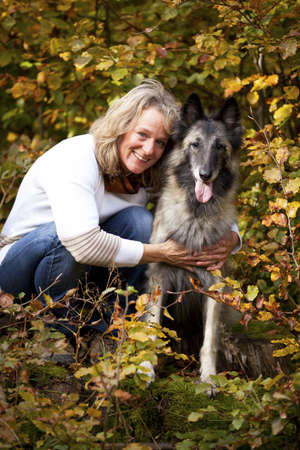 A portrait of a smiling blond woman with her belgian shepherd photographed in an autumnal forrest photo