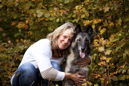A portrait of a smiling blond woman with her belgian shepherd photographed in an autumnal forrest