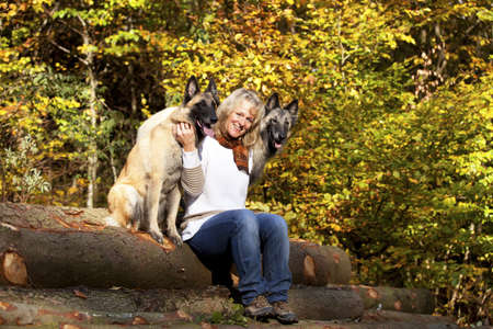 A portrait of a smiling blond woman with her two belgian shepherds photographed in an autumnal forrest Stock Photo - 8139136